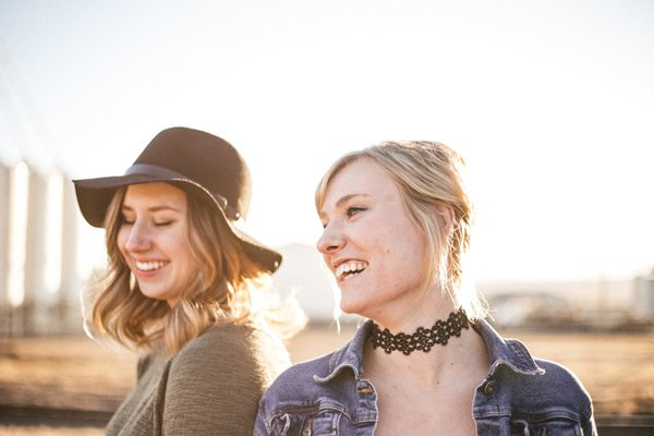 two smiling women outdoors in the sun