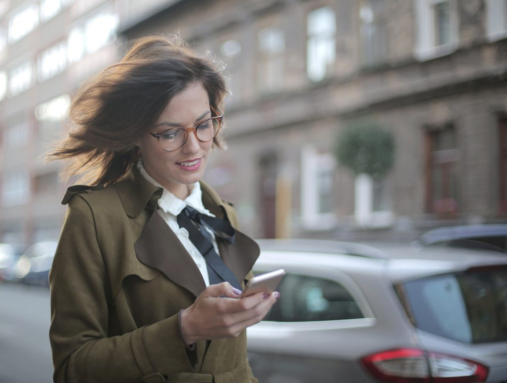 business woman on street reading phone
